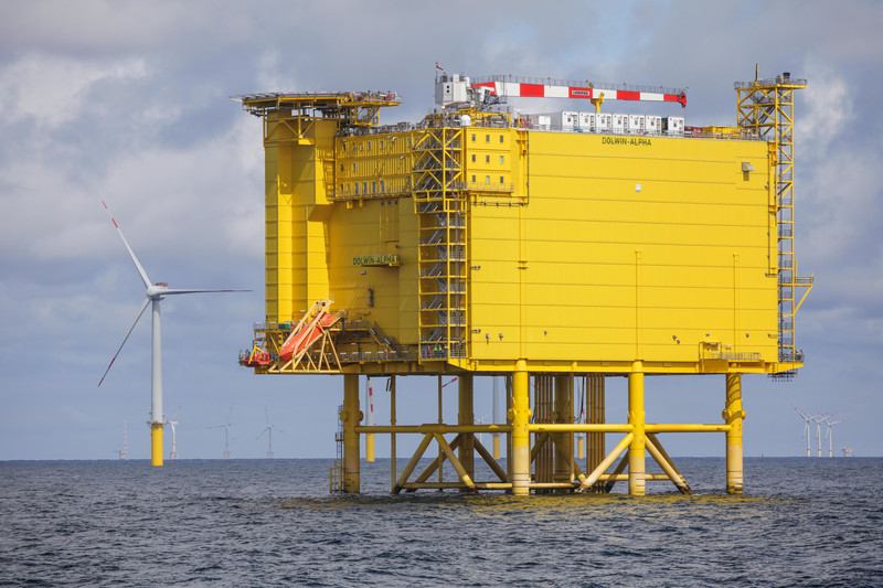 A yellow platform located at sea with some windmills in the background.