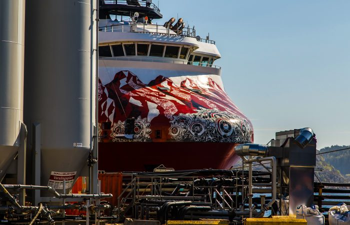 A red and white Ship is docking. Gass containers and tubes are in the foreground