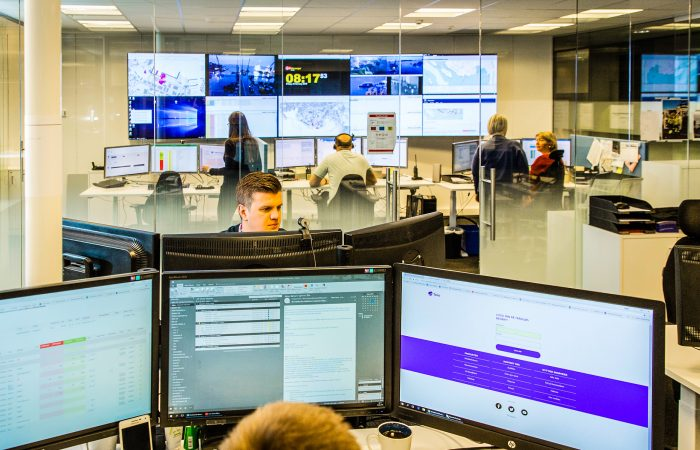 A logistics center. The image is taken over the head of an employee operating three screens. Other employees are working in the background and the wall behind everyone is covered in screens showing various data