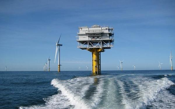 A white platform rising up from the sea at the princess Amalia wind farm, with windmills in the background.