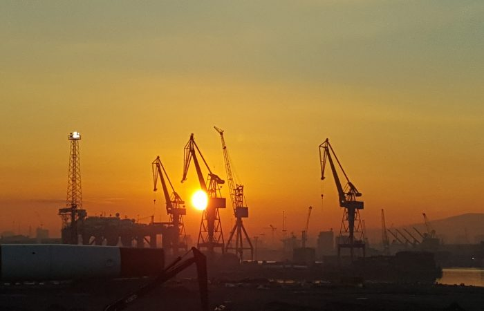 The sun is setting behind large cranes on a harbor