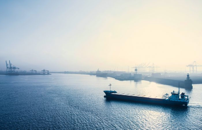 Et containerskip er på vei inn til havn. I bakgrunnen er det en rekke havner.