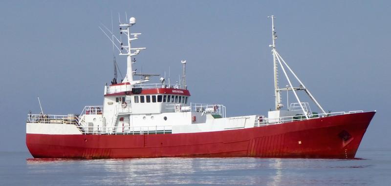 Et mindre rødt og hvit skip ute på havet.