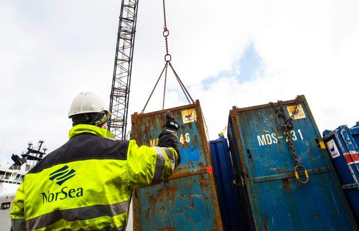En man i hvit hjelm og gul NorSea jakke veileder en kranfører som løfter en container.