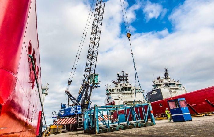 To rød og hvite skip er fortøyd i på en pir. En stor kran gjør seg klar til å løfte en stålkonstruksjon.