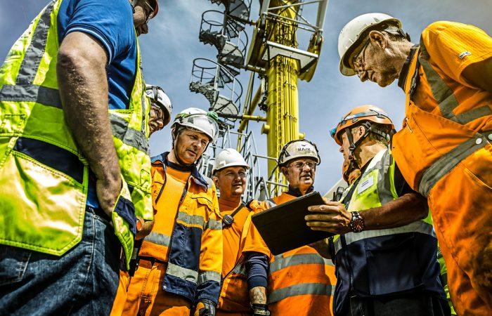 Arbedere i forskjellig arbeidsklær planlegger i en ring rundt et nettbrett.