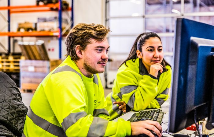 En mann og en kvinne i gule NorSea gensere studerer en pc skjerm.