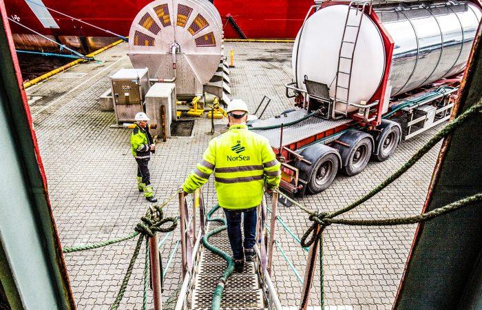 En mann i hvit hjelm og gul NorSea jakke er på vei ned en trapp fra ett skip mot en truck med drivstoff.