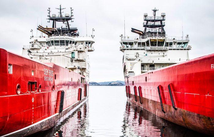 To hvite og røde skip ligger side ved side. Skjærgård kan sees i bakgrunnen.