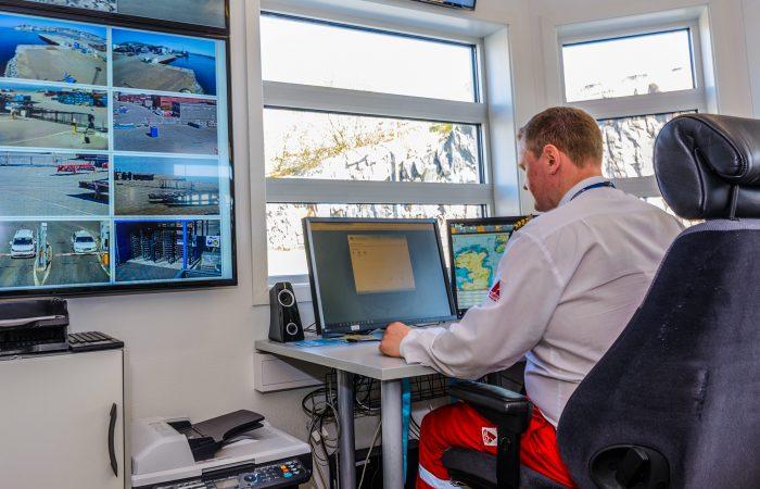 En mann sitter bak en pult inne i ett kontrollrom. På veggen henger en skjerm med overvåkningsvideo.