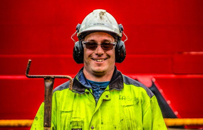 En arbeider i hvit hjelm, sikkerhetsbriller og gul jakke smiler til kamraet.