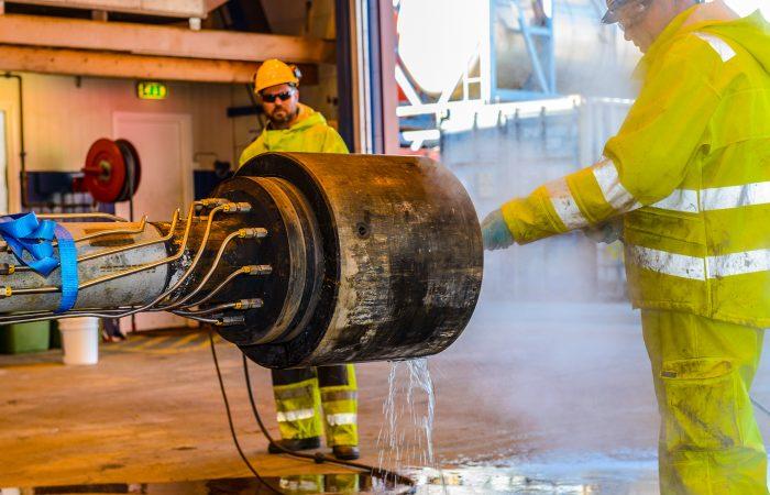 En mann i gule arbeidsklær sprayer teknisk rens på en rørdel.
