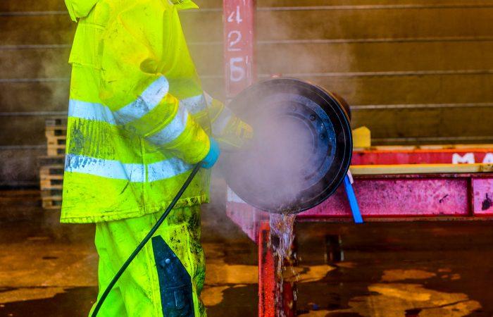 En person i gule arbeidsklær vasker en rørdel med teknisk rens.