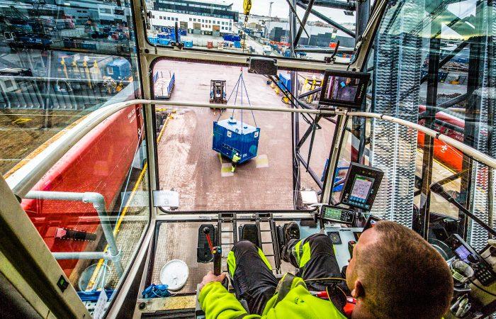 Bildet er tatt inne hos en kranfører og viser den blå containeren han løfter.