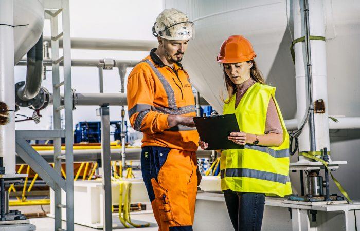 En mann i hvit hjelm og orange arbeidsklær og en kvinne i orange hjelm og refleksvest planlegger bak en notatblokk.