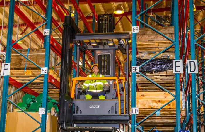 En mann i gul hjelm og grønne arbeidsklær opererer en stor gaffeltruck inne på ett lager.